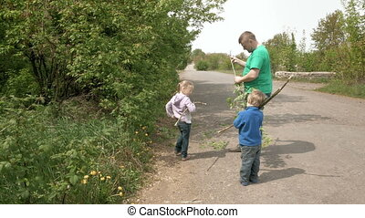 Father and happy children play with rods outdoors - Father...