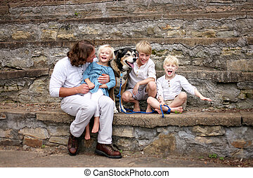 Father and Happy Young Children and Pet Dog Sitting On Stone Stairs on Summer Day
