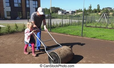Father and helper girl level ground with roller in townhouse...