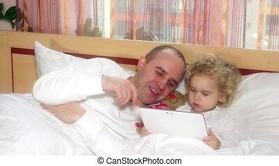 father and her cute daughter lying on bed looking in digital tablet