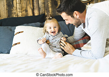 Father and his baby daughter on bed having fun