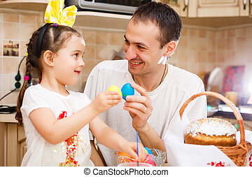 Father and his daughter are painting eggs. Happy family preparing for Easter. Cute little child girl wearing bunny ears.