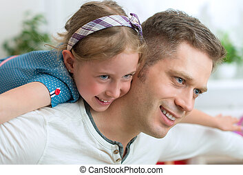 Father and his daughter playing at home.
