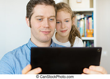 Father and his daughter using tablet pc.