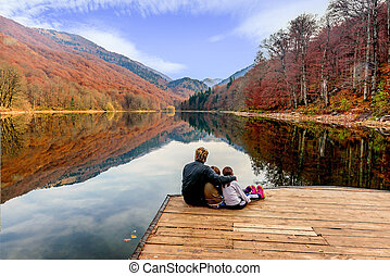 Father and his daughters enjoying the view of Lake Biograd (Biogradsko jezero), Biogradska Gora national park in autumn, Montenegro
