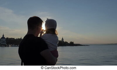 Father and his little daughter are looking at a beautiful sunset. River in the city center