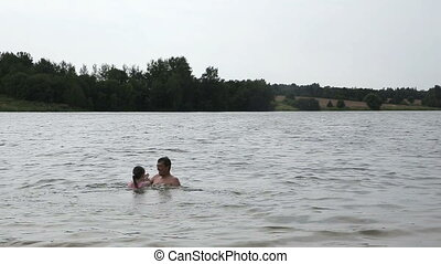 Father and his little daughter having fun on lake