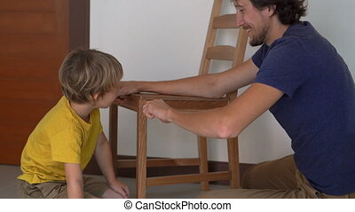 Father and his little son are assembling furniture. They...
