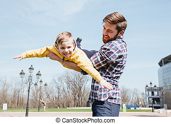 Father and his little son playing together in a park