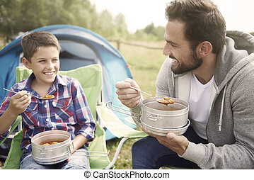 Father and his son eating dinner on camping
