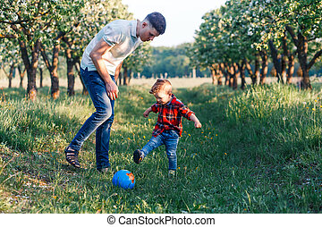 Father and his son having fun outside in summer hugging and laughing. Father taking care of his child