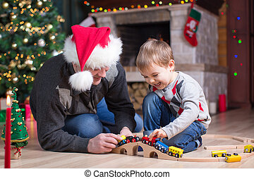 Father and his son play with model railway near christmas tree
