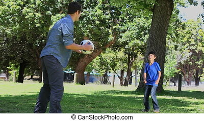 Father and his son playing football