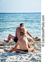 father and his son playing in sand on sea beach