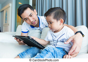 Father and his son playing with tablet computer at home.