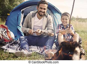 Father and his son spending time together on camping
