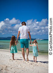 Father and his two kids walking by the sea