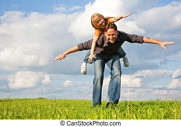 Father and his kid - daughter - playing together at a meadow, he is carrying her piggyback