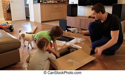 Adult man kneeling on floor and reading manual while assembling new furniture with children near cute dog