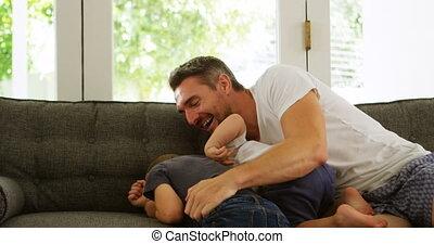 Father and kids having fun on sofa 4k
