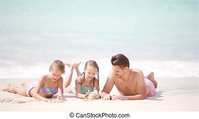 Father and kids lying on white beach - Father and kids...