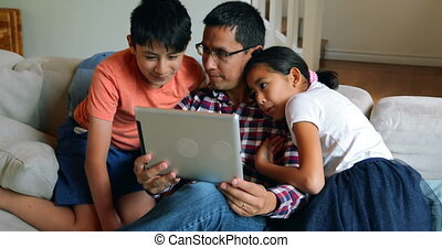 Father and kids using digital tablet in living room 4k