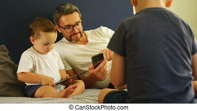 Father and kids using mobile phone and digital tablet on bed...