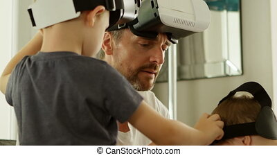 Father and kids using virtual reality headset at home 4k -...