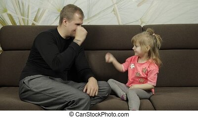 Father and little daughter playing rock paper scissors on sofa. Leisure game