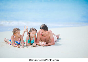 Father and little kids enjoying beach holidays