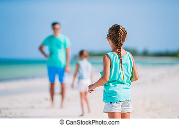 Father and little kids on the beach