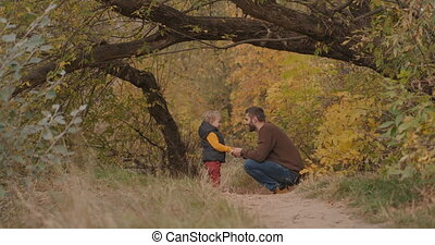 father and little son are spending time in picturesque autumn forest, walking and communicating together at weekend, happy childhood and fatherhood