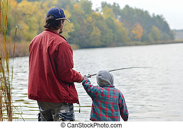 Father and little son fishing together on autumn day