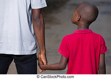 father and little son holding hands walking on a road.