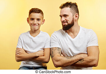 father and little son smiling at camera isolated on studio background
