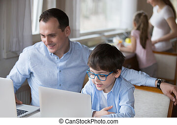 Father and little son using laptop sitting at home