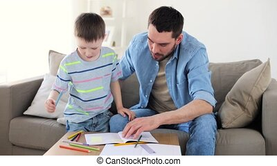 father and little son with crayons drawing at home - family,...