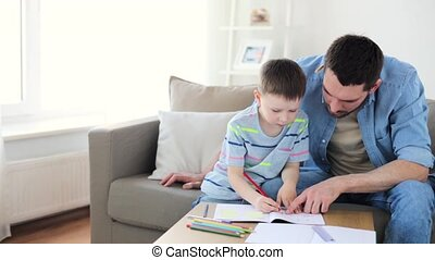 father and little son with crayons drawing at home