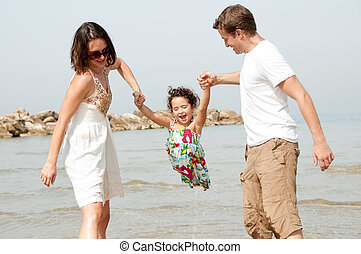 father and mother hold the daughter