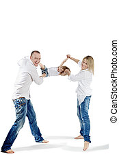 Father and mother in the white shirts and blue jeans swing their little daughter for hands and for feet, all three laugh cheerfully.