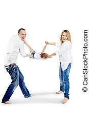 Father and mother in the white shirts and blue jeans shake the child for hands and for feet and laugh cheerfully.