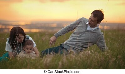 Father and mother play with her son, the baby sitting on the grass with a toy, summer evening in nature