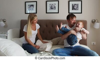 Father and mother playing with boy two years lying in bed.