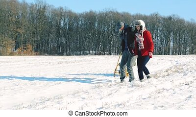 Father and mother pulling daughter on sledge, running.
