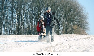 Father and mother pulling daughter on sledge, running. ...