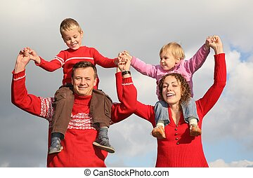 father and mother stand, holding children on the shoulders