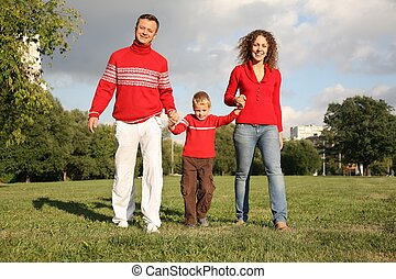 father and mother walk, holding son for the hands