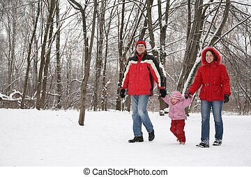 father and mother walk in park with child at winter