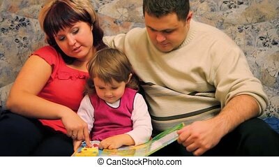 father and mother with little daughter read children\'s book