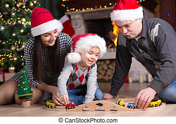 Father and mother with son play with model railway near christmas tree